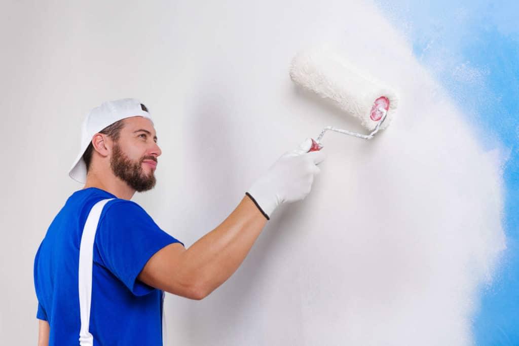 Handwerker mit blauem T-Shirt streicht eine Wand weiß.