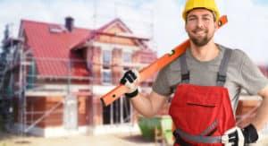 Bauarbeiter mit rotem Overall steht vor Rohbau.