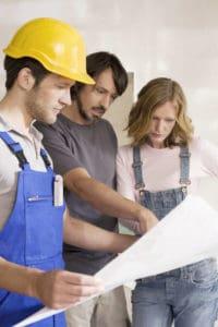 Junges Paar schaut sich gemeinsam mit einem Handwerker Baupläne an.
