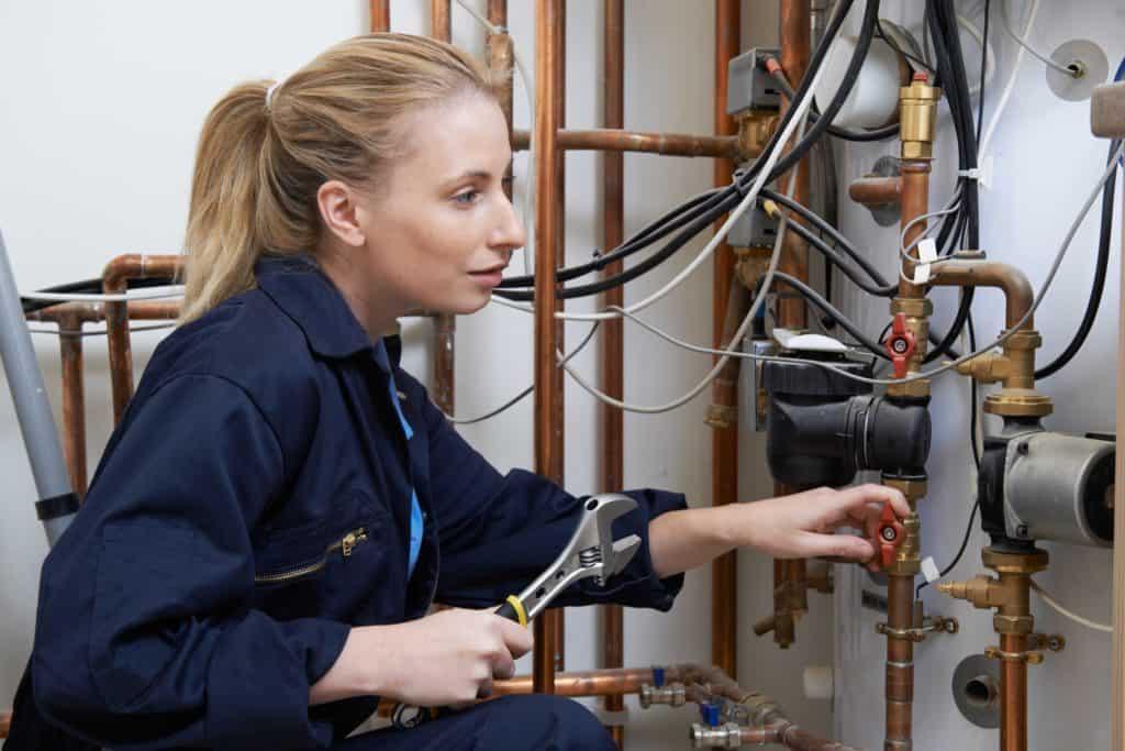 Ausbildung: Junge Frau im blauen Overall mit Rohrzange in der Hand betrachtet ein Rohrsystem an der Wand.