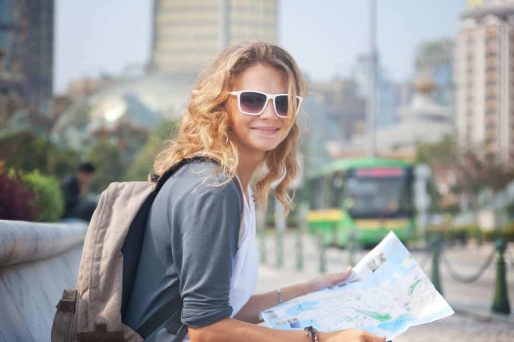 Reisen mit kleinem Budget: junge Frau mit Rucksack und Stadtkarte in der Stadt.