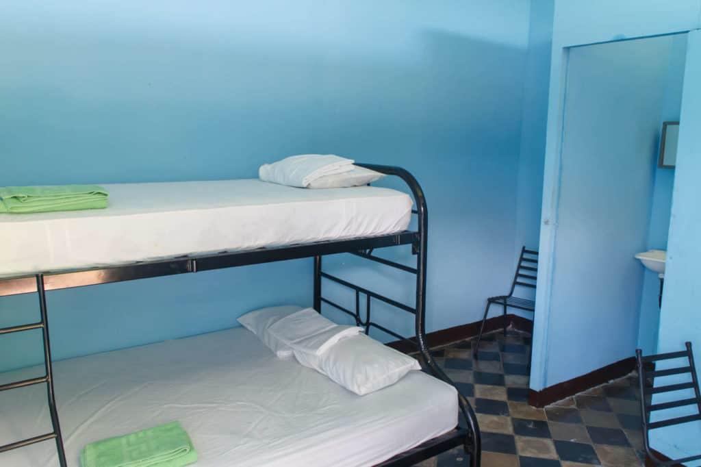 Reisen mit kleinem Budget: Hostelraum mit Etagenbett, karg eingerichtet.