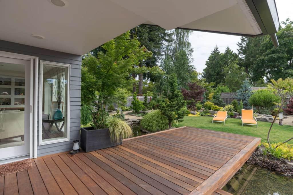 Eine Holzterrasse verbindet harmonisch Haus und Garten.