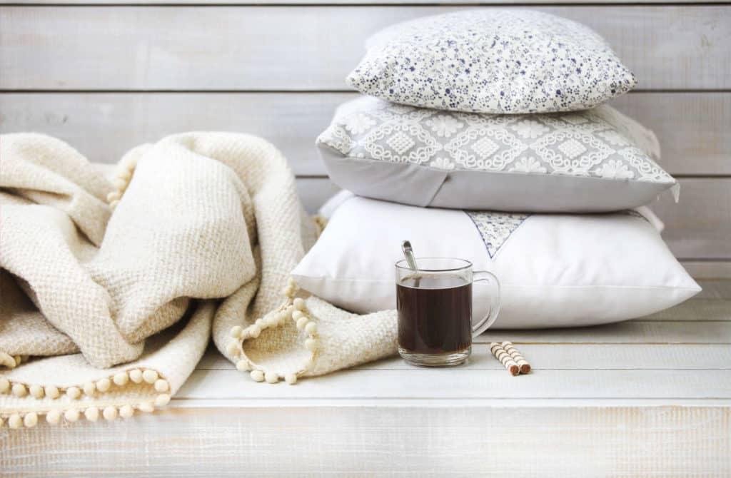 Landhausstil: Eine Wolledecke, kissen Tee und Kekse auf Holz: Einladung zum Entspannen.