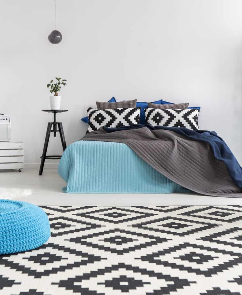 Schlafzimmer, in dem die Muster der Kissen auf den Teppich und die Farbe des Poufs auf die Tagesdecke abgestimmt sind.