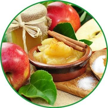 Apfelmus mit Zimzstange in einer Schüssel mit riten Äpfeln und Apfelmusglas.