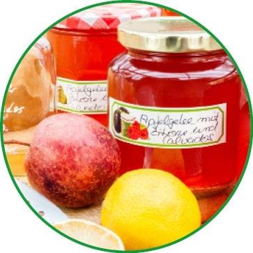 Zwei Gläser mit Apfelgelee und roten Äpfeln und einer Zitrone davor.