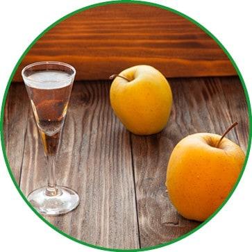 Ein Glas Calvados mit 2 gelben Äpfeln auf Holz.