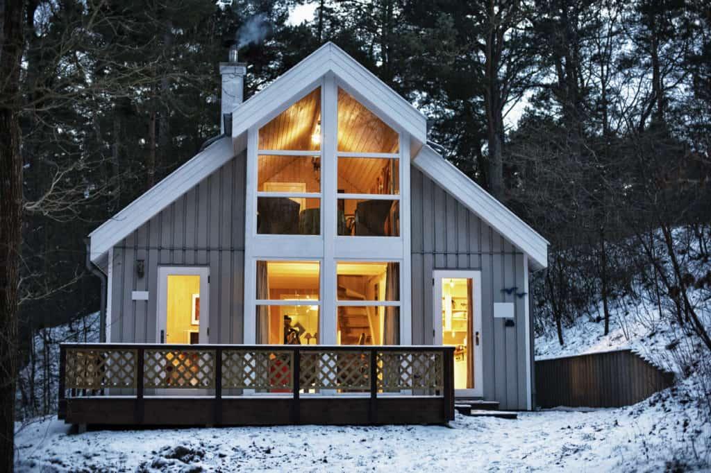 Graues Haus mit weißen Fenstern in Holzbauweise zwischen Bäumen im Schnee.