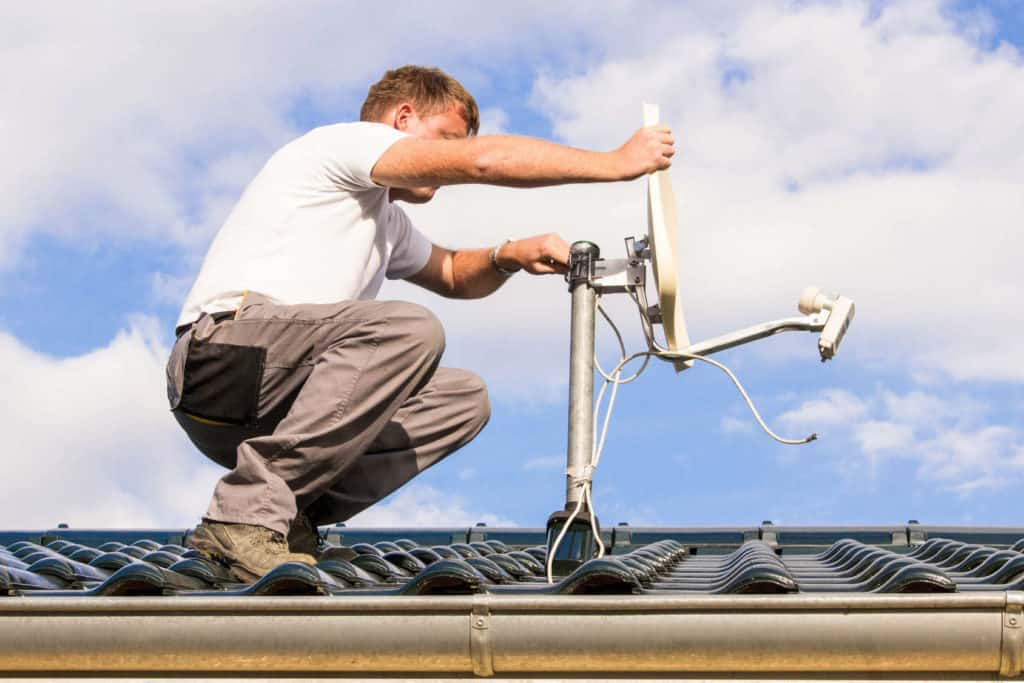 Handwerker überprüft auf dem Dach die Satellitenschüssel. Winterchek für das Haus