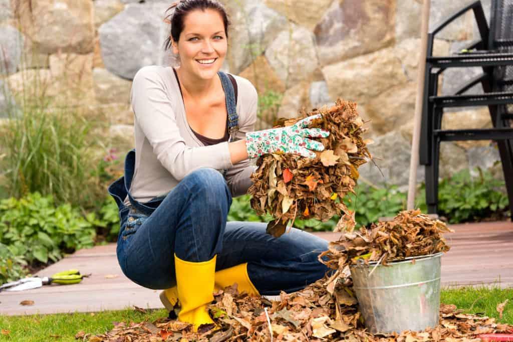 Frau sammelt Laub in einem Metalleimer.