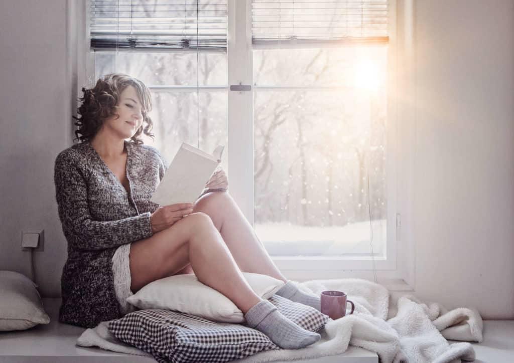 Frau sitzt in Wolljacke und Wollsocken mit nackten Beinen am Fenster bei einer Tasse Tee und liest, während die Wintersonne ins Haus scheint.