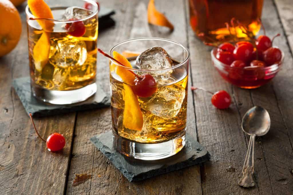 Old Fashioned Cocktail mit Kirschen, Eis und Orangen.