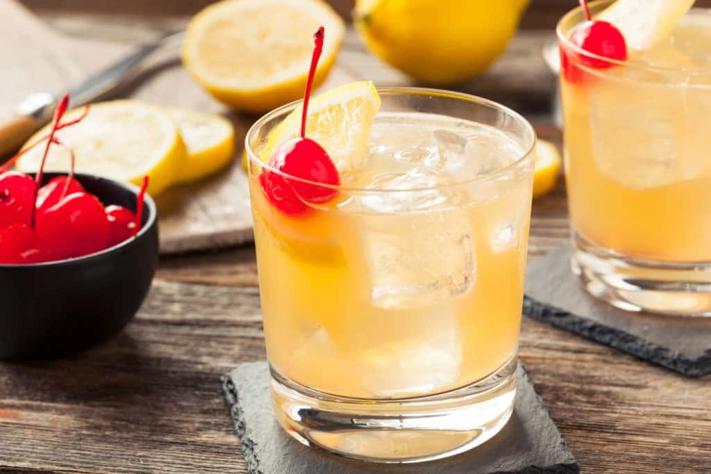 Whisky Sour im Glas mit Zitronenscheibe, Kirsche und Eis.
