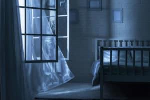 Durch die geöffneten Fensterläden eines verlassenen Schlafzimmers lässt der Wind eine Gardine wehen.