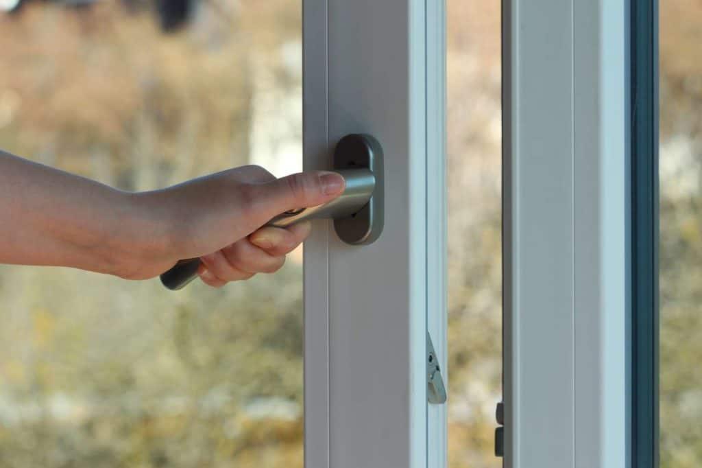 Eine Hand öffnet ein Fenster.