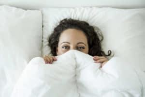 Brünette Frau liegt sich im weiß bezogenen Bett und hat sich die Bettdecke bis über die Nase hochgezogen.