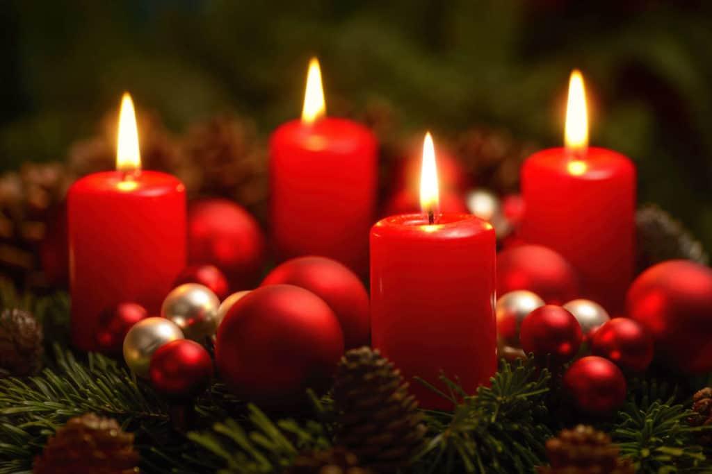 Adventsbräuche: Ein Adventskranz mit roten Kerzen und Tannenzweigen