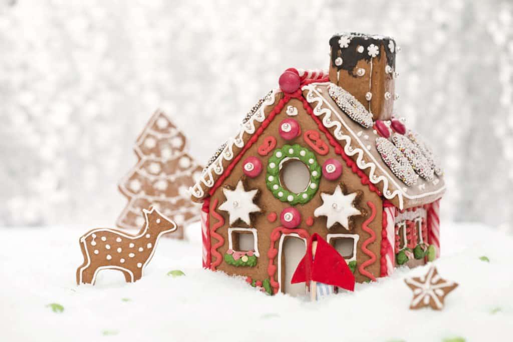 Adventsbräuche: Lebkuchenhaus mit Reh und Tannenbaum aus Lebkuchen in Schnee-Dekoration