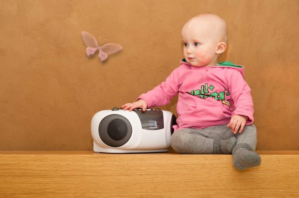 Bauen mit Lehm: Kleinkind mit CD Player vor einer bräunlichen Lehmwand.