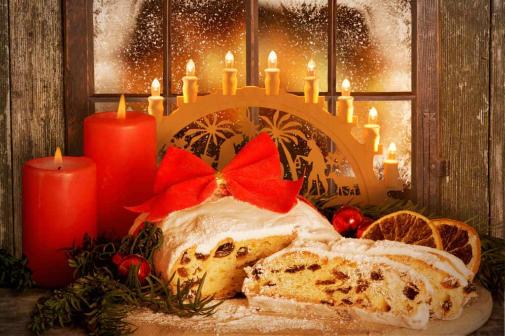 Adventsbräuche: Tannenzweige, Christbaumkugel, Stollen, rote Kerzen und ein Lichtbogen in einem Fenster.