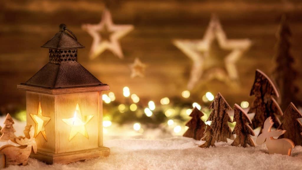 Adventsbräuche: Weihnachtliche Szene aus Holz im Laternenlicht