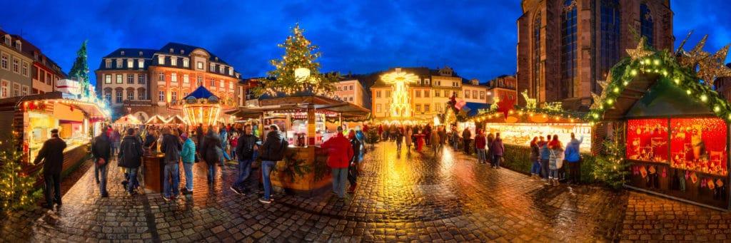 Adventsbräuche: Der Heidelberger Weihnachtsmarkt mit seinen Ständen und Besuchern als Panoramaaufnahme.
