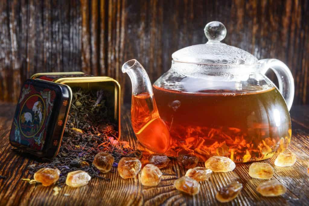 Gläserne Teekanne mit rötlichem Tee und Kandiszucker.