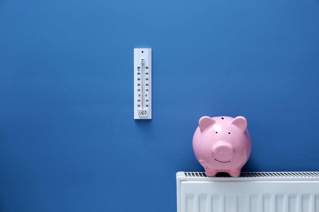 Ein rosa Sparschwein steht auf einer Heizung vor blauem Hintergrund, an der Wand hängt ein Thermostat.