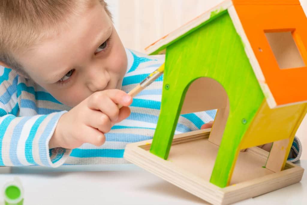 Vögel füttern: Ein kleiner Junge bemalt ein Vogelhaus aus Holz mit knalligen Farben.