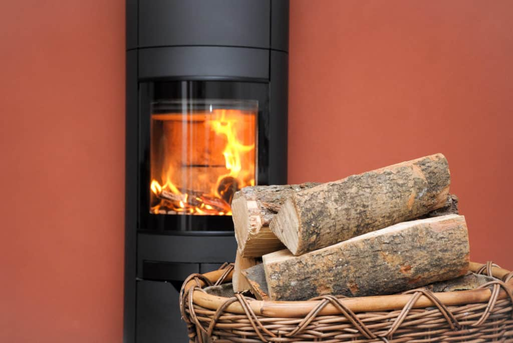 Feuer in schwarzem Kaminofen. Davor ein Korb mit Brennholz für den Kamin.