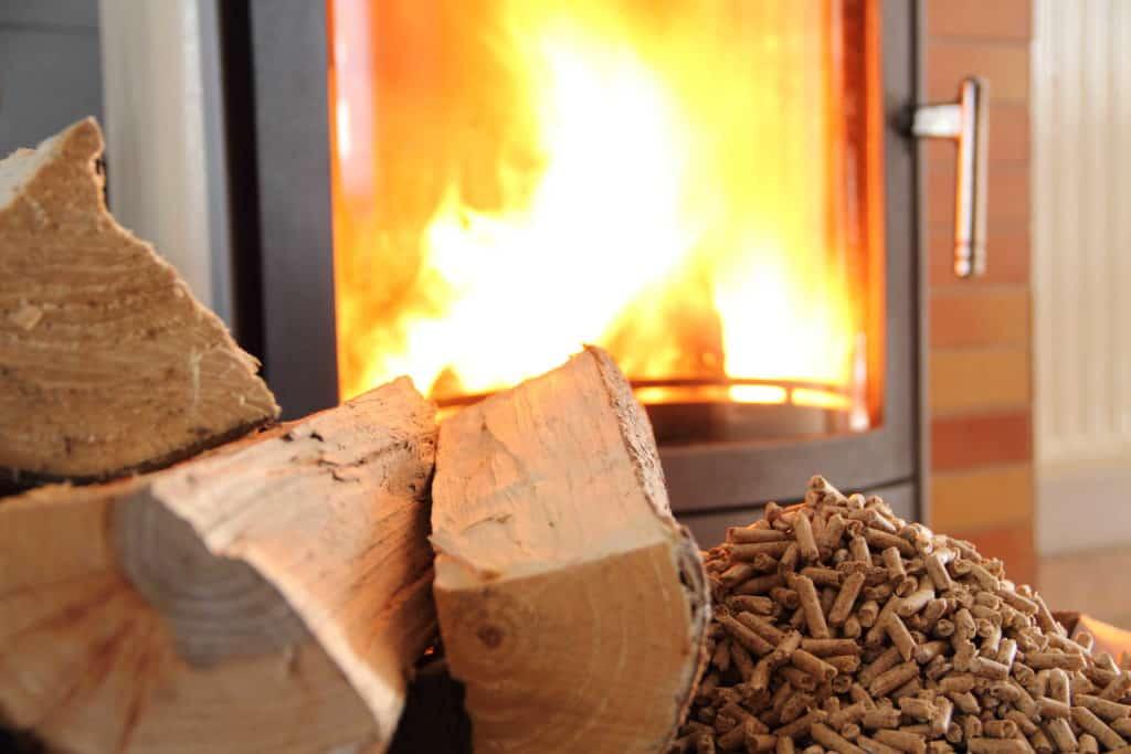 Pelletofen mit lodernden Flammen. Davor Holzscheite und Pellets. Brennholz für den Kamin.