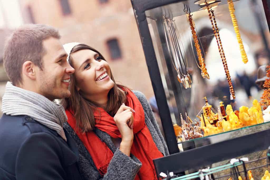 Sanfter Tourismus achtet auf unbedenkliche Souvenirs. Junges Paar vor einem Stand mit Bernsteinketten, die problemlos gekauft werden können.