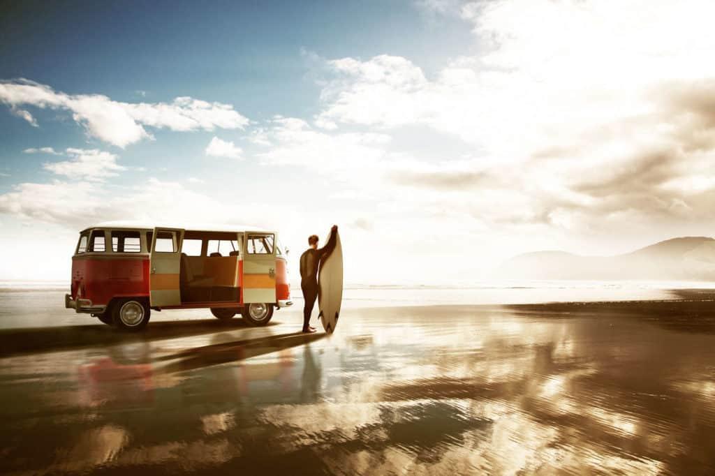 Sanfter Tourismus: Surfer mit Surfbrett vor einem VW-Bus schaut in die Wellen und die Sonne.
