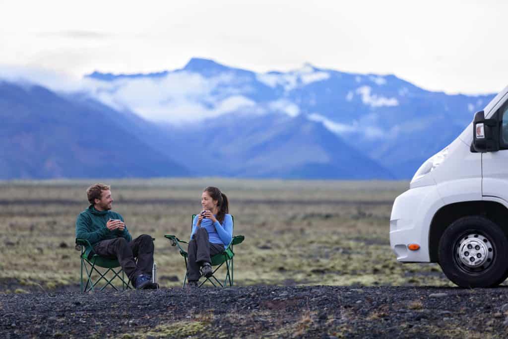 Sanfter Tourismus: Junges Paar in Klappstühlen in einer Gebirgslandschaft neben dem Wohnmobil.