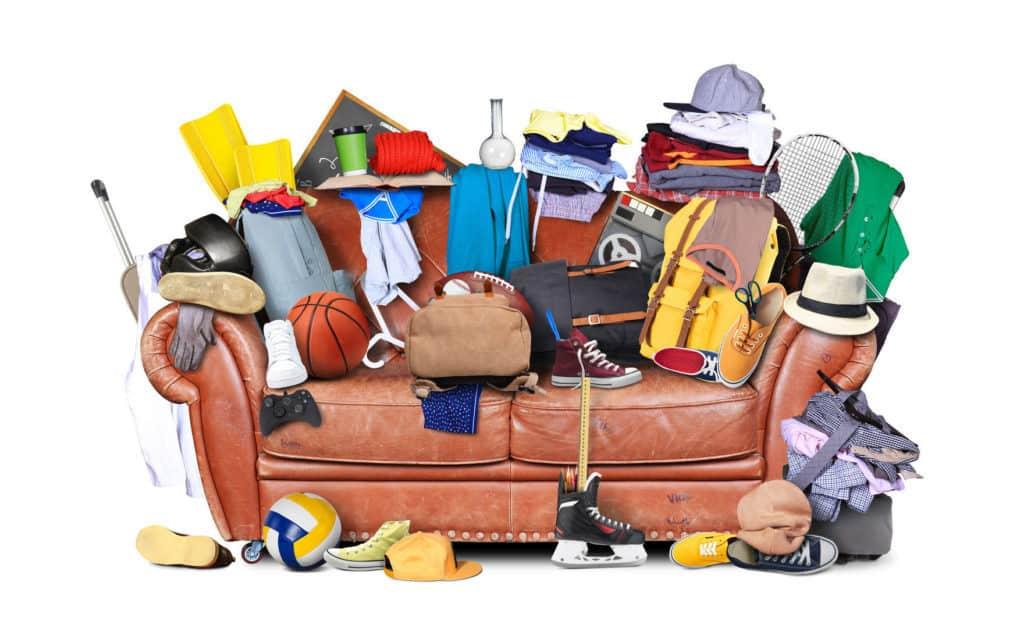 Entrümpeln: Sofa mit altem Krempel wie Schuhe, Bällen Taschen und Kleidungsstücke.