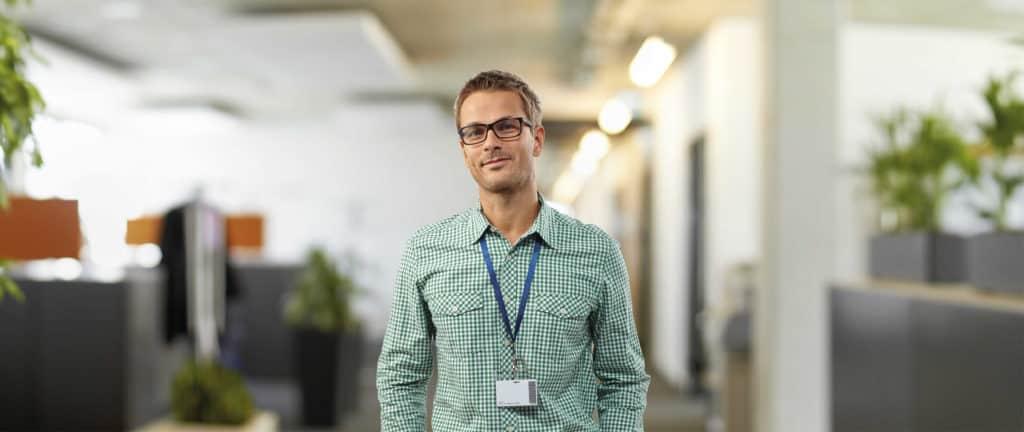 Junger Mann mit Hemd und Brille vor hellen Büroräumen.
