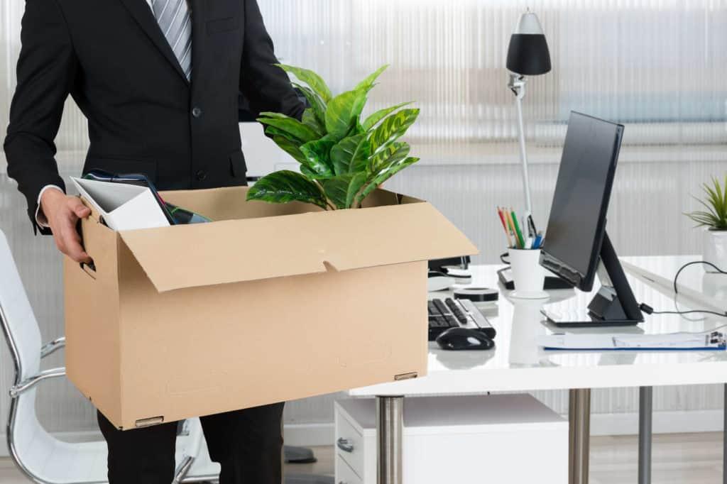 Job-Bewertungen: Ein Angestellter trägt einen Karton mit seinen Büroutensilien.