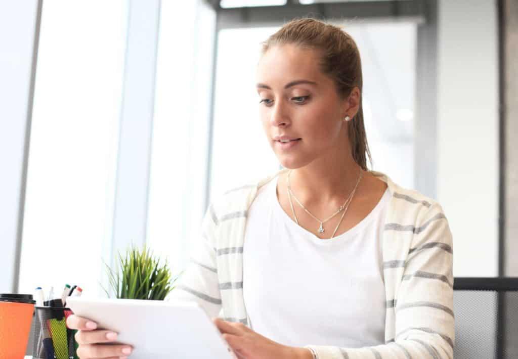 Job-Bewertungen: Junge Frau surft mit ihrem Tablet im Internet.