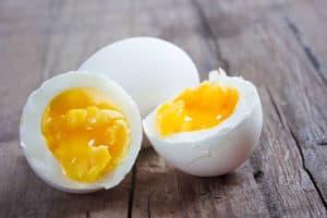 Lebensmittel-Lifehacks, Nummer 5: Auf einem Holztisch liegt ein ganzes und ein halbiertes gekochtes Ei