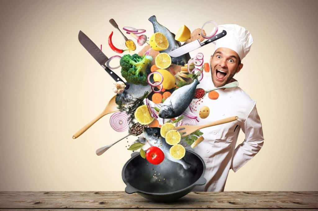 Lebensmittel-Lifehacks: Ein Koch wirft mit einem Wok verschiedene bunte Lebensmittel in die Luft.