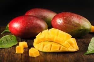 Lebensmittel-Lifehacks, Nummer 1: Drei Mangos und eine halbe, aufgeschnittene Mango liegen auf einem dunklen Holztisch.