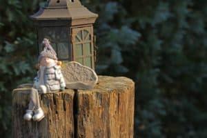 Auf einem Baumstumpf steht eine Laterne, daneben ein Stein und eine Porzellanpuppe.