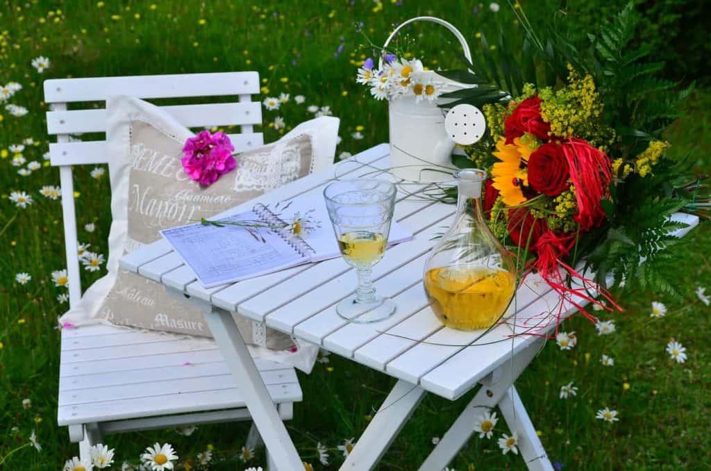 Eine romantische Ecke im Garten schaffen Sie mit Holzmöbeln und Blumen im Handumdrehen.