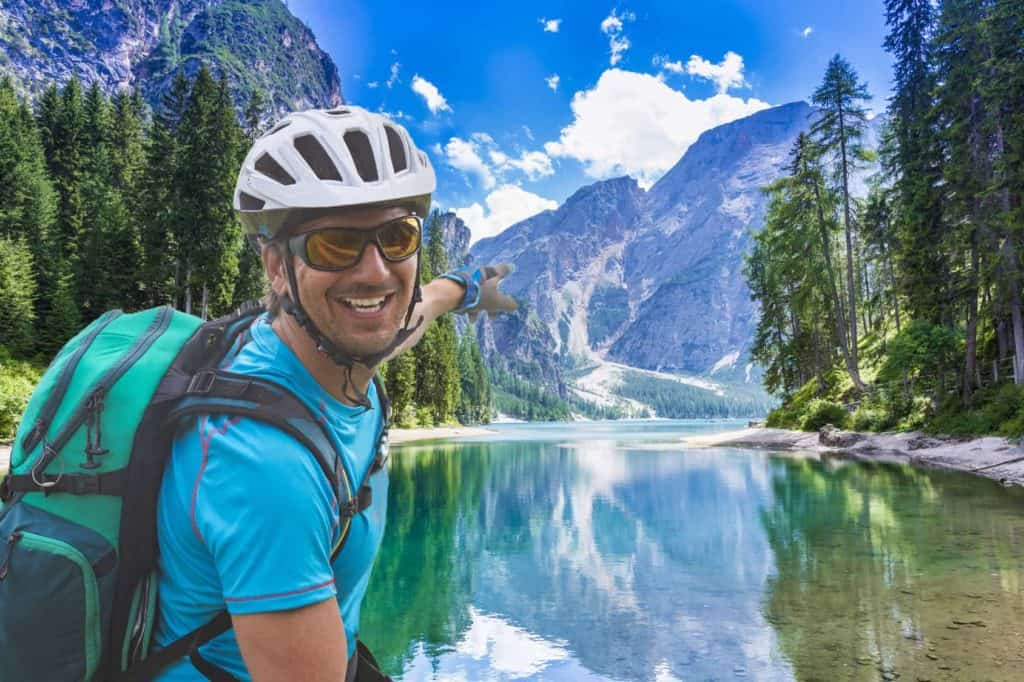 Radreise: Radler in sportlicher Radlerkleidung mit Helm vor einem See und Gebirge.