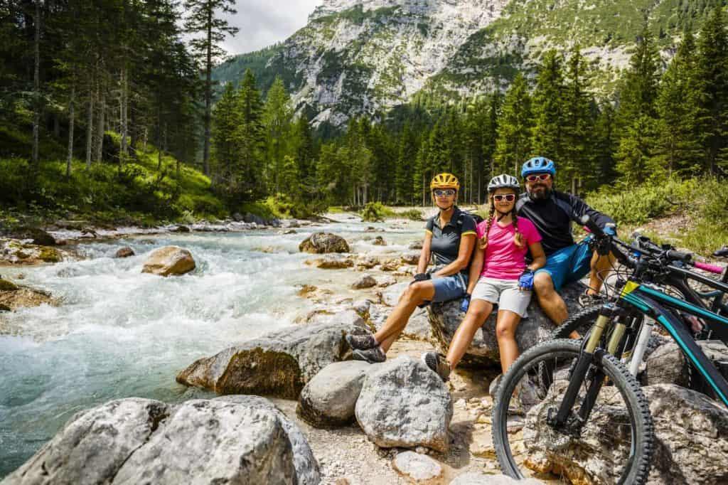 Radreise: Vater, Mutter und Tochter mit Fahrrädern bei einer Rast an einem Gebirgsbach.