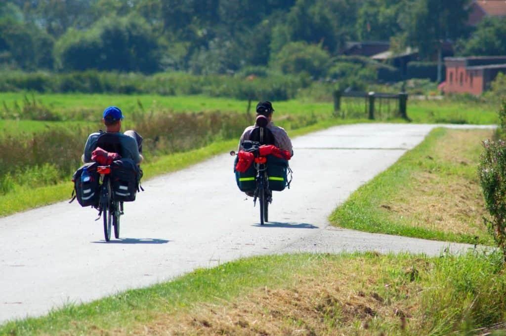 Zwei Männer auf Liegerädern von hinten auf einer Straße fotografiert. Radreise