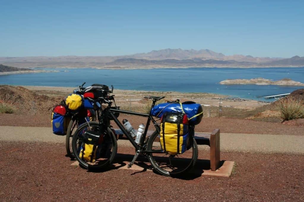 Radreise: 2 Trekkingräder mit bunten Satteltaschen. Im Hintergrund der lake mead in den USA