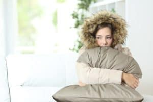 Frau mit Jacke und Kapuze unklammert frierend ein Kissen, weil die Heizung ausgefallen ist