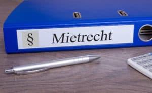 Beratung ist wichtig: Auf einem Schreibtisch liegt ein Ordner zum Mietrecht, ein Kugelschreiber und ein Taschenrechner.